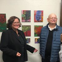 Artist Michael Gurney standing in front of his displayed artwork with Mayor Cathy Murillo