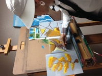 Artist Erin Ziegler painting yellow trees on canvas on easel