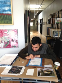 Artist Nelson Riveria in the gallery at a table drawing looking down at his work