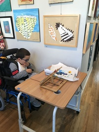 young boy in wheelchair sitting at desk with small easel and paint