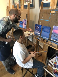 young boy in white shirt and dark hair sitting in front of an easel with paintbrush in right hand and Instructor Jacob standing behind him