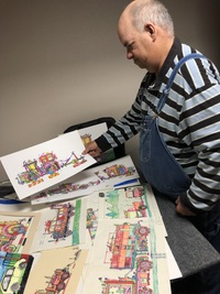 Artist Kyle Allan sitting in his studio holding up one of his tractor drawings