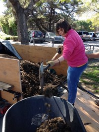 Julie wearing pink sweater and jeans shoveling dirt for garden at Applied Abilities Program