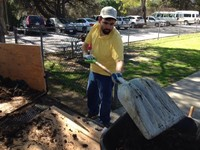 Nelson wearing yellow sweater white cap and jeans shoveling dirt for garden at Applied Abilities Program