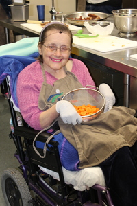 Joy in pink sweater and brown apron holding bowl of chopped carrots in cooking class