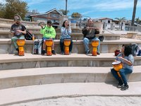 group of five participants with drums sitting outside in music class in Santa Maria Applied Abilities Program