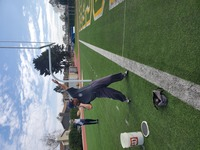 man in sweats standing on football field and participating in Santa Barbara Special Olympics