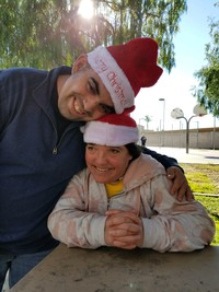 two participants in red Santa hats hugging outside