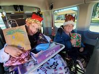 participants in red and green Christmas hats sitting in van and holding gifts