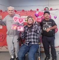 three men pose for Valentines celebration holding heart decorations at Santa Maria Applied Abilities Program