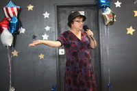 woman with microphone singing at Santa Maria Applied Abilities Talent Show