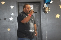 one man in black shirt with microphone in his hand singing in talent show