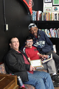 three men sitting in library and smiling at Santa Maria Applied Abilities Program