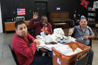 three men sitting at table and folding towels at Santa Maria Applied Abilities Program