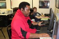 man in red sweatshirt sitting at computer in life-skills training at Santa Maria Applied Abilities Program