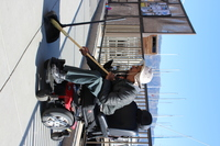 JJ is a man in a wheelchair with a large brimmed tan hat and sweeping the sidewalk near the marina
