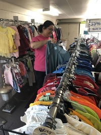 woman wearing a pink shirt is hanging up clothes at Alpha Thrift Store