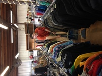 man in red sweater sweeping in the clothing aisle at Alpha Thrift store