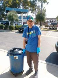 man in blue shirt and cap pulling a trash can at Santa Maria CHP