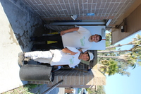 two men with Harbor Crew shirts standing in front of a restroom ready to clean it
