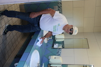 man with white shirt jeans and white cap and sunglasses wiping down and cleaning a restroom sink
