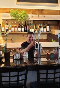 Carlos standing behind a bar and serving drinks at the restaurant he works at in Santa Maria