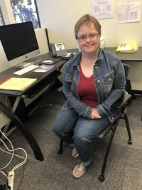 Sara wearing jean jacket and red shirt sitting in office chair where she works at the Independent Resource Center