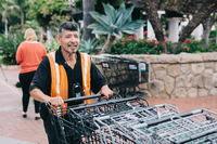 Luis wearing a black shirt and orange safety vest while pushing grocery carts at Ralph's
