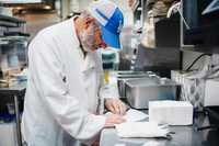 man in blue cap and white chef coat folding napkins in the kitchen at Jeannine's Bakery