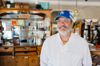 man in blue cap and white chef coat standing in Jeannine's Bakery where he works