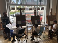 three children sitting in chairs at easels watching Instructor Jacob in Children's Adaptive Arts Program