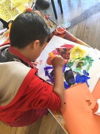 young boy in red sweatshirt and dark hair painting a color wheel that has glued on photos of fruit
