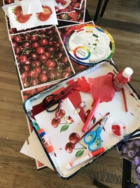 a table with a white tray of all red art supplies color wheel scissors crayons paints and photo of cherries