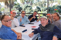 seven men sit at a table for the Harbor Crew Holiday Celebration
