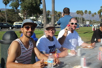 three men sitting outside at a picnic table eating at the Harbor Crew Taco Party