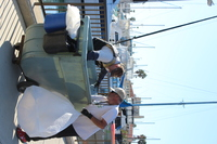 two Harbor Crew members pushing trash cart and holding plastic bags ready to remove trash