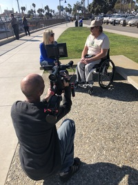 Brian sits in a wheelchair next to a woman who is interviewing him while another man films with a large video camera