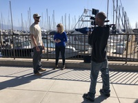 Matt stands next to woman who is interviewing him near the marina while another man films
