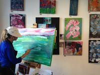 Artist Erin Ziegler painting a large landscape canvas painting inside the studio with art hanging on wall behind her