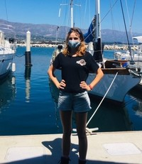 UCP WORK, Inc's Job Coach Corina Powell standing in the marina wearing a facemask and jean shorts with hands on her hips