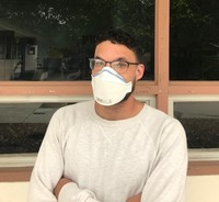 UCP WORK, Inc. Job Coach Johnathan Plummer standing outside the Applied Abilities office wearing a white facemask