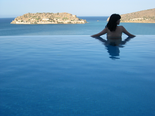 Greco-Roman Goddess, Cynthia Daddona, enjoying a private room with its own infinity Pools at Elounda's Blue Palace Hotel with Spinalonga Island in the distance