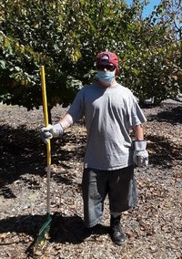 Kelly Kilroy is in a grey shirt and shorts and red cap and holding a rake and wearing work gloves.