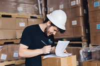 a person wearing a white construction hat and navy tshirt and holding a clipboard and pen in a warehouse.