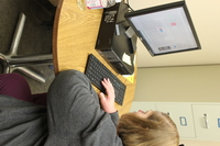 a person sitting at a desk looking at a computer and typing on the keyboard.