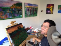 Joe Haake sits at an easel with an acrylic landscape painting in front of him, he's smiling at the camera.