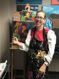 Erin Ziegler holding a paintbrush and standing in her studio near an easel with an acrylic abstract painting