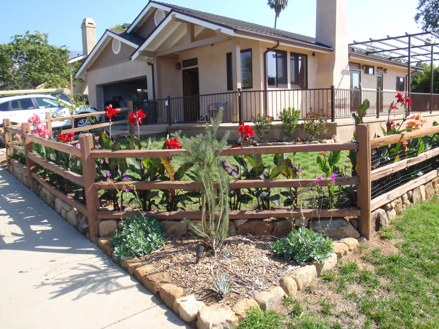 front yard buffalograss lawn stonework split rail fence plantings