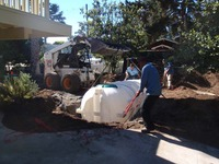 lowering rainwater tank into ground