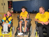 one girl one boy and adult male in yellow shirts and wheelchairs